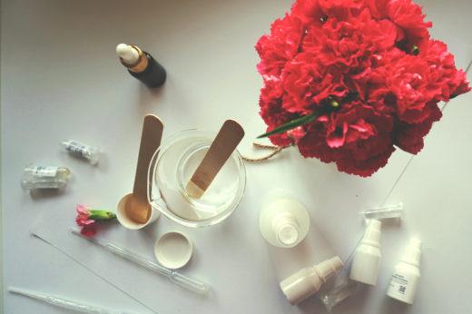 Na białym biurku, różowe gożdziki, surowce naturalne w opakowaniuach i zlewka z jakąś substancją przeźroczystą w środku z drewnianą szpatułką.