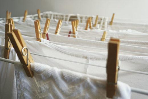 Białe pranie na suszarce przyczepione za pomocą drewnianych klamerek.
