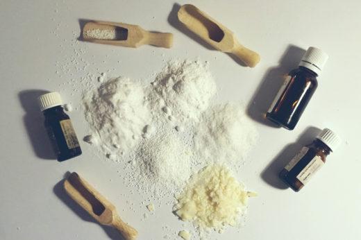 Na białym biurku znajdują się rozsypane proszki i płatki mydlane, a w koło nich olejki eteryczne i szpatułki drewniane.