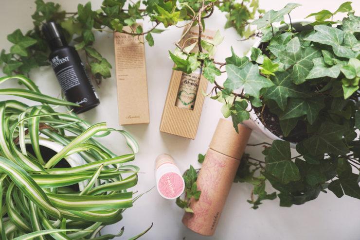 cztery naturalne kosmetyki na białym biurku przy nich 2 zielone kwiatki doniczkowe.