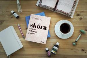 """Opisywana książka na biurku, obok herbata, olejki do twarzy, notes i inna otwarta książka. - Recenzja książki """"Skóra- azjatycka pielęgnacja po polsku""""- Meivy.pl"""