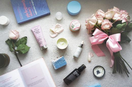 Kosmetyki naturalne na białym materiale, po prawej bukiet róż. Po lewej na górze i na dole książka a po środku po lewej stronie jedna różowa róża.