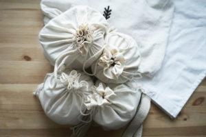 Na drewnianym biurku pełne woreczki przydatne do zakupów, a pod nimi torby na zakupy.