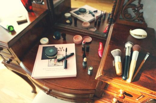 Drewniana tolateka stylizowana na starą, ze żłobieniami, a na niej różowa książka i naturalne kosmetyki do makijażu i pędzle.