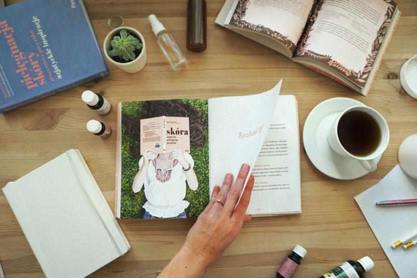 """Opisywana książka otwarta na biurku, obok herbata, olejki do twarzy, notes i inna otwarta książka. - Recenzja książki """"Skóra- azjatycka pielęgnacja po polsku""""- Meivy.pl"""