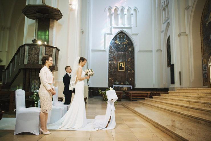 Martyna z Mężem (zdjęcie od boku wiec męża nie widać) w sukni ślubnej w katedrze, a za nimi świadkowie..