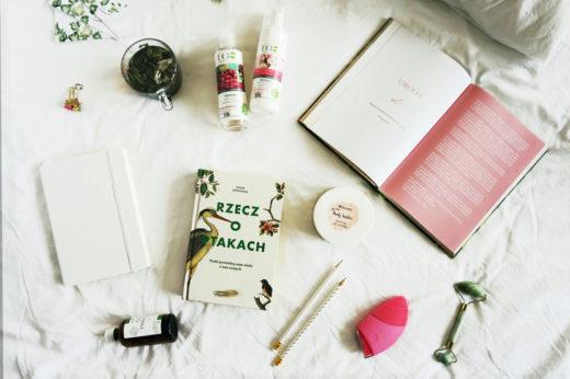 """Na białej pościeli koemstyki, książka """"Rzecz o ptakach"""", druga książka otwarta z napisem """"Uroda"""", herbata liściasta w kubku, notes, ołówki, masażer do twarzy i szczoteczka soniczna do twarzy."""