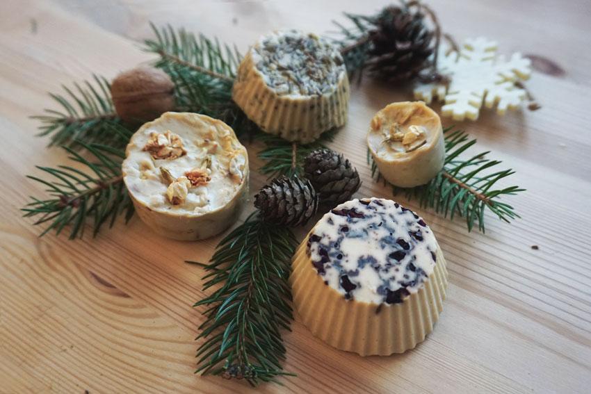 Mydełka handmade na drewnianym stole, udekorowane szyszkami i gałązką choinkową. - Prezenty świąteczne DIY w duchu Zero Waste - Meivy.pl